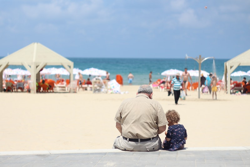 grandparent with grandchild on the beach