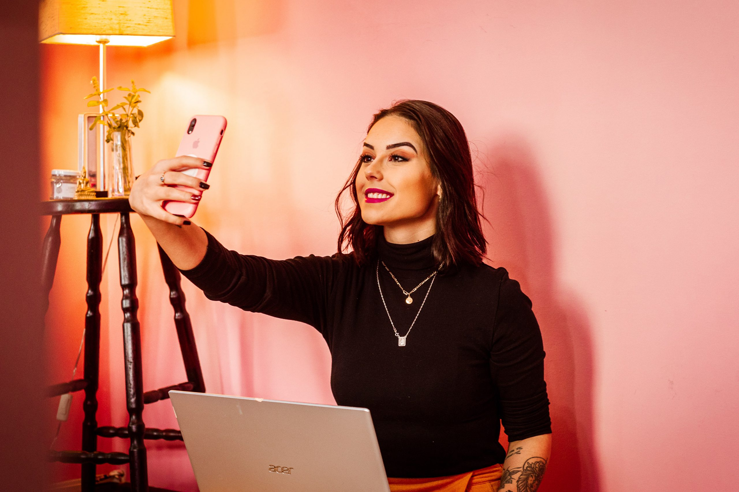 Women making selfie in pink room while sitting behind a laptop