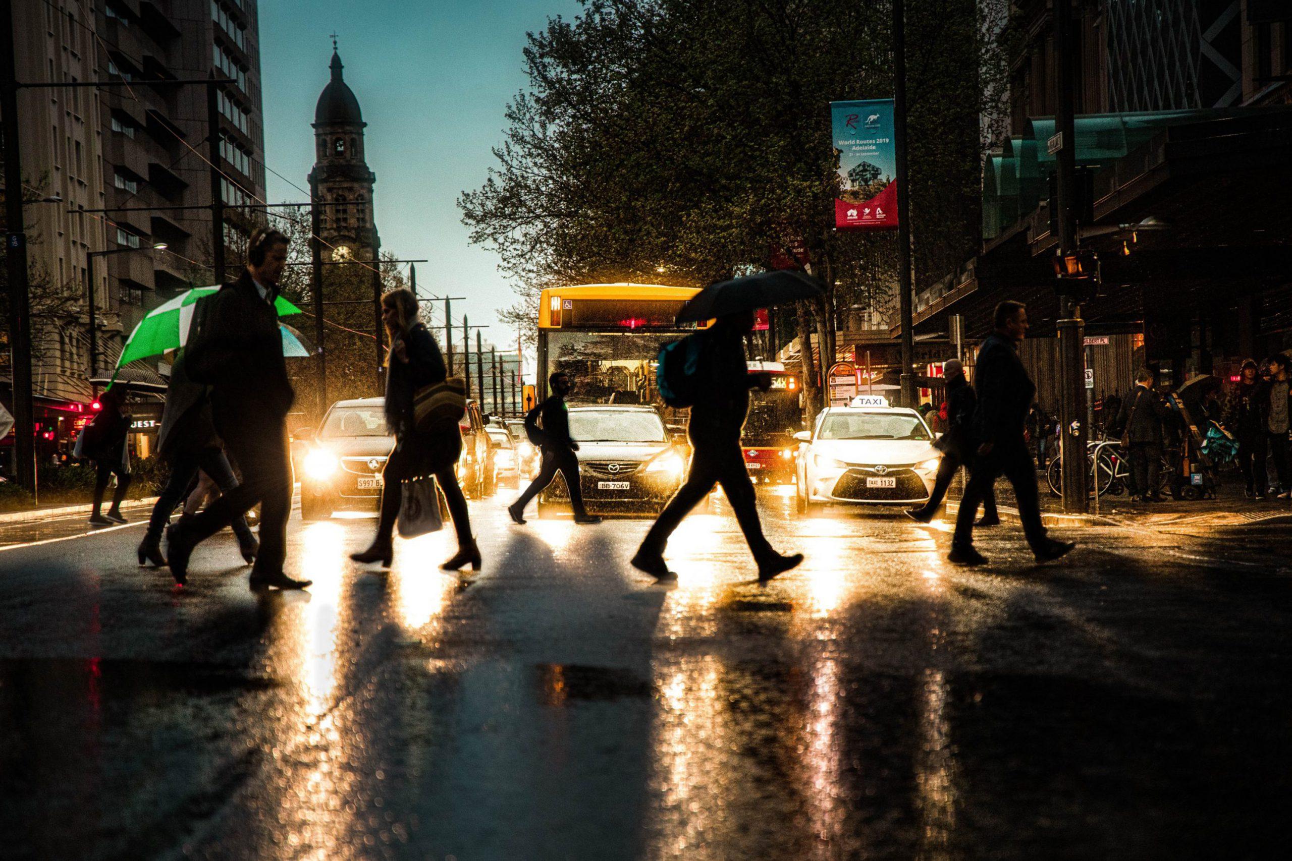 People-walking-on-pedestrain-lane-during-a-rainy-evening