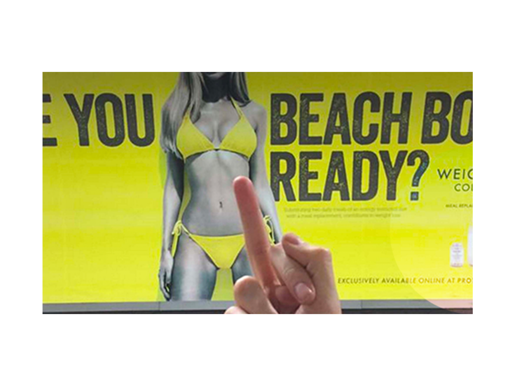 Women on billboard with text: Is your body beach ready? Someone in stand in front of the billboard and puts his middle finger up