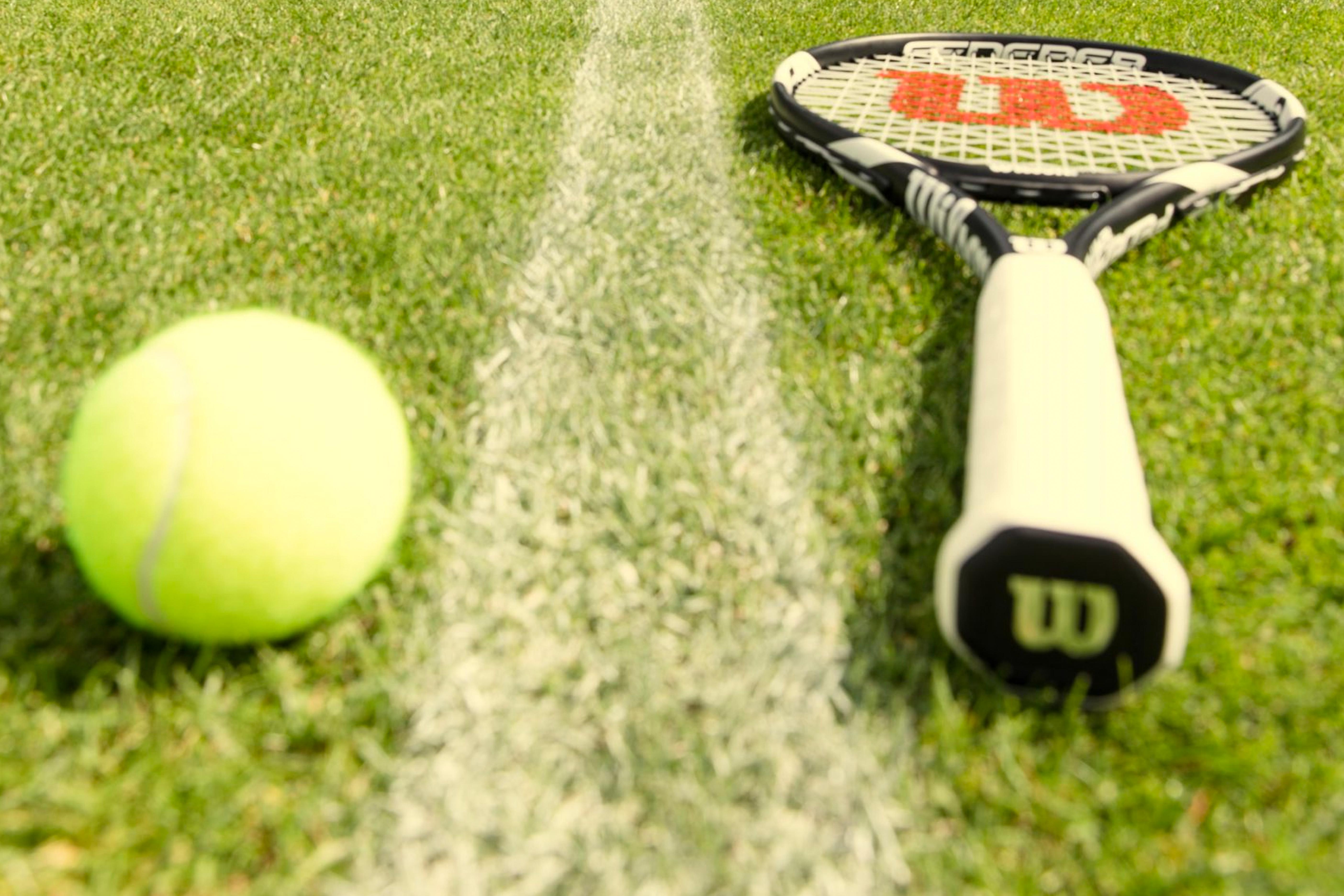 Tennis-racket-on-grass-and-bal